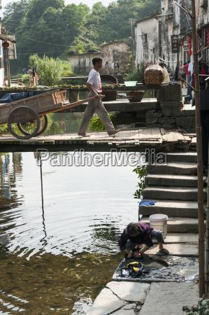 a man pulls his wooden cart