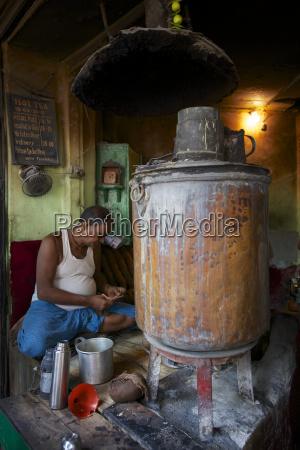 indian chai wallah with cauldron of