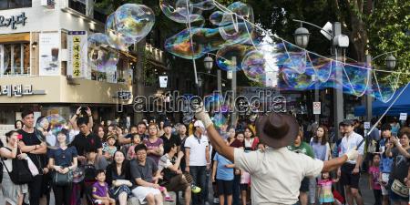 spectators watch a street performer make