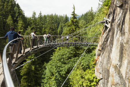 tourists walking on the capilano suspension