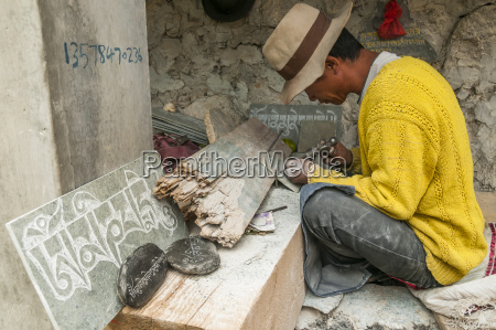 worker carving stones with the mantra
