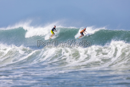 a pair of surfers ride a