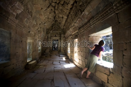tourist looking trough temple window in
