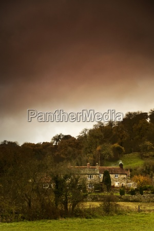 country houses dramatic sky in background