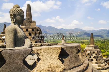 buddha statue amidst the latticed stone