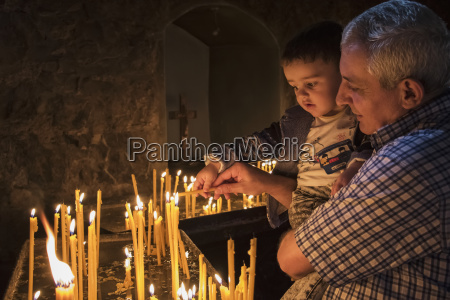 man holding a boy lighting candles