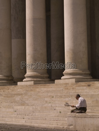 man readning newspaper stairs with columns