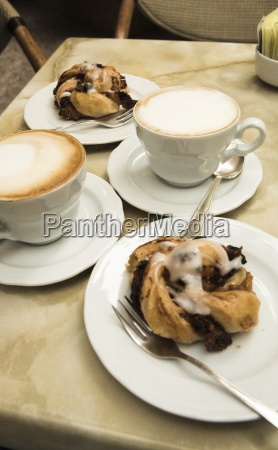 two cappucinos and dessert on table