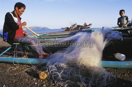 man repairing fishing net iloilo panay