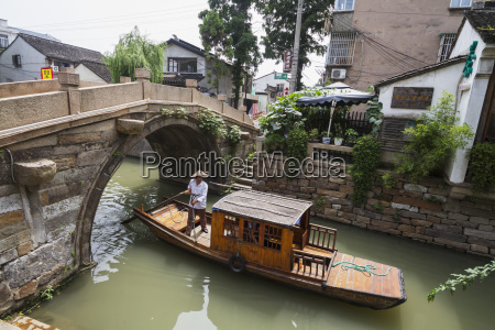 man punting a boat by a