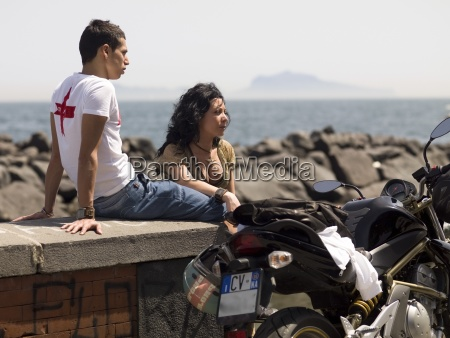 mid adult couple sitting on promenade