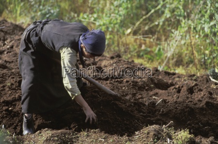 person working the land by hand