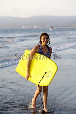 woman on beach carrying bodyboard