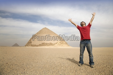 man standing near the pyramids with