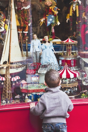 small boy looking in toy shop