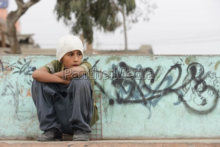 young boy by wall of graffiti