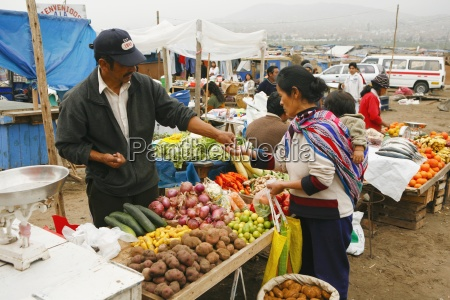 purchasing fresh vegetables from market stall
