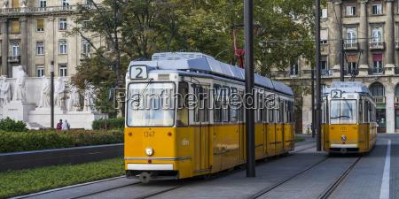 a yellow tram runs on a