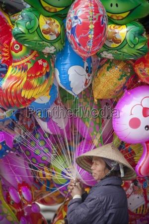 person holding many balloons hanoi vietnam