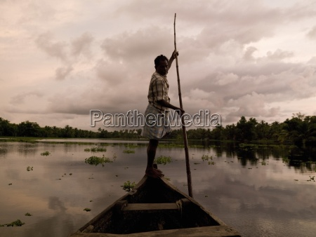 man punts down alleppey backwaters alleppey