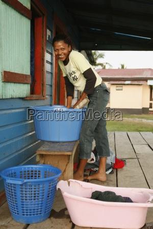 woman washing hands in bucket tasbapauni