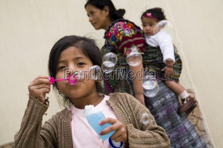 girl blowing bubbles with a bubble