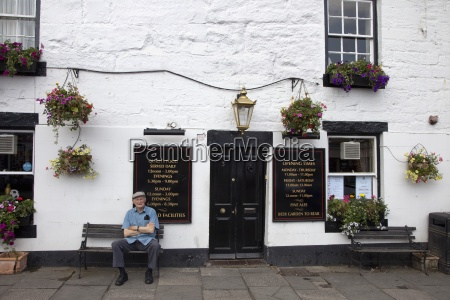 a man sitting outside a restaurant