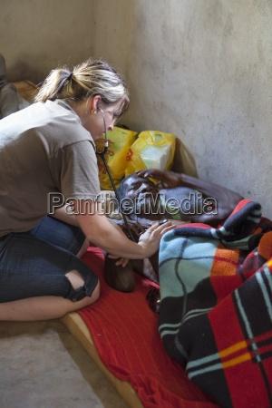 a nurse checks a man dying