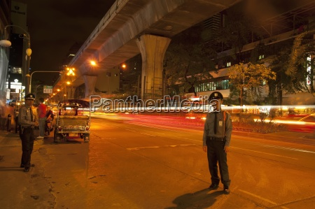 guards help guide traffic on silom
