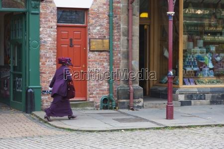 a woman dressed in purple walks