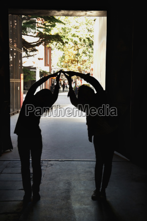 two people forming a bridge with