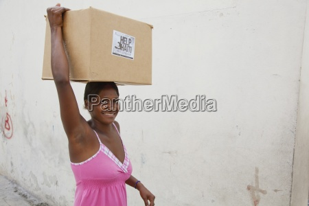 a woman carries a box on