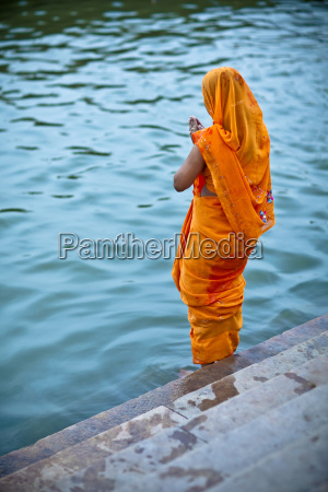 a woman offers prayers on the