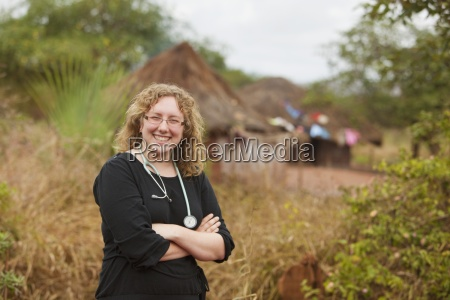 a physician stands outside a village