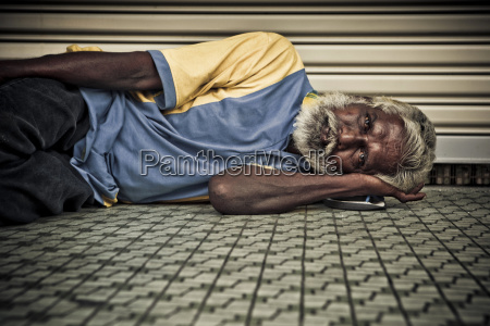 a homeless man rests on the