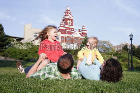 two daughters play with parents in