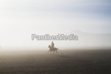man riding a horse in the