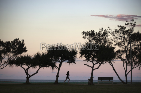 silhouette of a woman running along