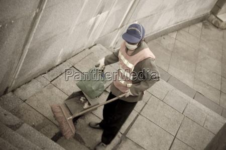 young woman sweeping up garbage guangxi