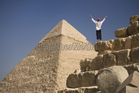 a woman tourist raises her arms