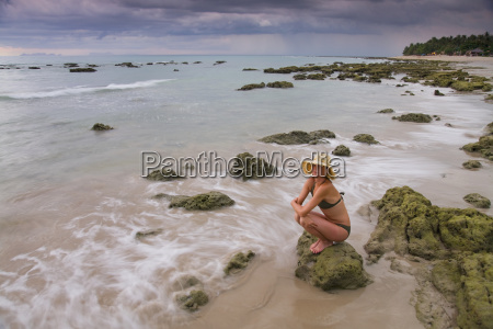 a woman tourist crouches on a