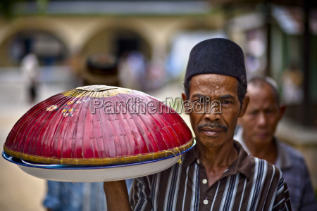 a man carries a large bowl