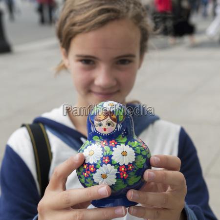 a girl holds a matryoshka nesting