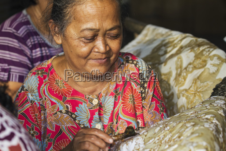 craftswoman drawing intricate patterns by using
