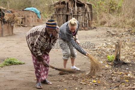 two women working together to sweep