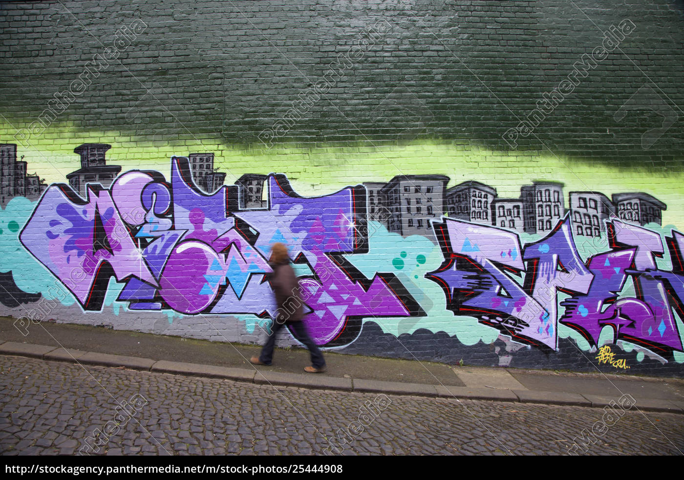 Rights Managed Image 25444908 A Pedestrian Walking Along A Graffiti Covered Wall