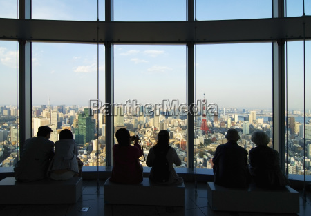 people in silhouette watching the tokyo