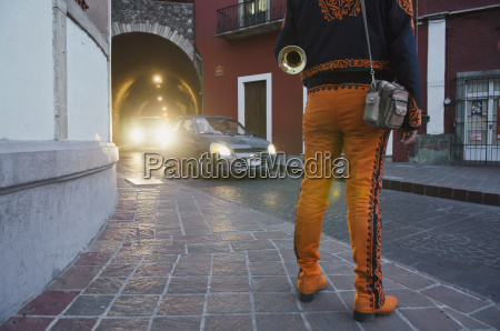 trumpet player wearing orange mariachi outfit