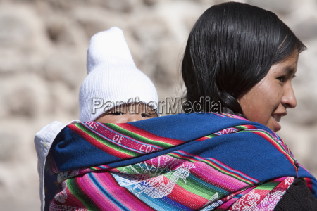aymara woman carrying a baby on