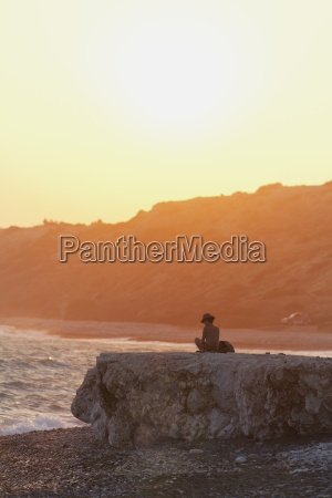 woman wearing bikini and sunhat sitting
